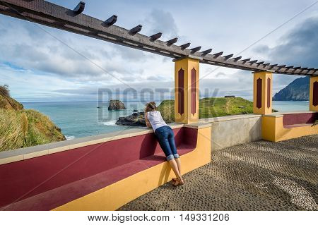 Woman looking at the ocean view from colorful viewpoint building. Porto da Cruz, Madeira island, Portugal.