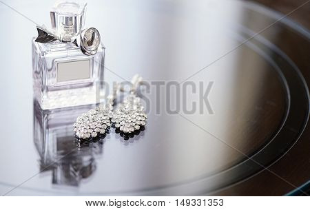 Beautiful wedding rings and perfume bottle for bride and groom. Beauty of wedding accessories indoors. Close-up bridal jewellery and perfumery. Female and male jewel. Jewelry for man and woman