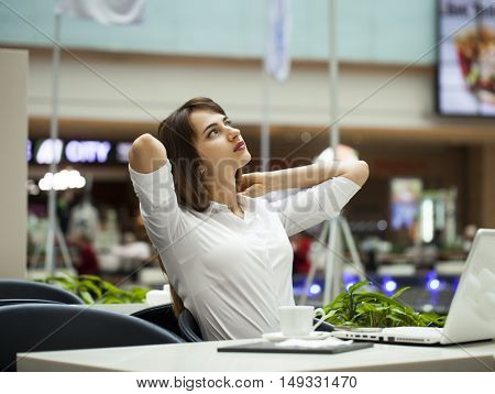 Young beautiful business woman drinking coffee while sitting in a restaurant