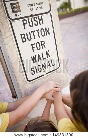 Children pressing a button at traffic lights on pedestrian crossing and having fun on a sunny summer day. push button to cross street. Teamwork.