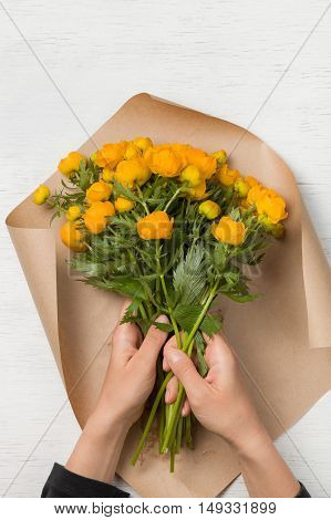 Young woman making a bouquet of yellow flowers. Top view on girl's hands preparing birthday bouquet on white wooden background. Lifestyle concept.