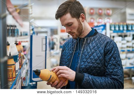 Handsome handyman or DIY renovator standing in a hardware store purchasing supplies and reading a label on a product