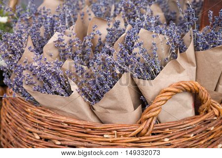 Top view on beutiful fresh lavender flowers in the basket on the street market. Bunches of lavender in craft paper. Romantic flowers.