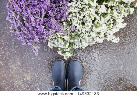 Top view on man's legs in blue rubber boot standing close to a basket with beautiful garden flowers. after rain. Pink purple and white flowers in bouquet. Man choosing flowers on the street market.