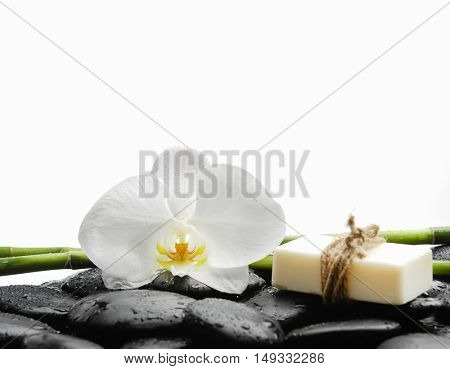 White orchid with black stones ,grove,soap on wet background