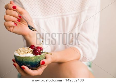 Closeup of woman's hands holding a cup with organic yogurt with oats and cherries. Homemade vanilla yogurt in girl's hands. Breakfast or snack. Healthy eating and lifestyle concept.
