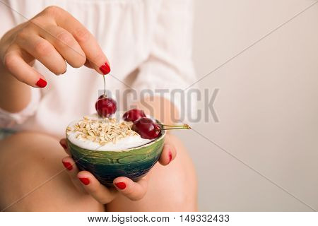 Closeup of woman's hands holding bowl with organic homemade yogurt topped with oats and cherries. Hands with cup of vanilla yogurt served with granola and berries. Healthy dairy snack or breakfast
