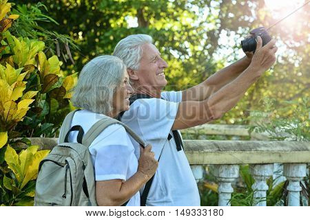 Beautiful happy elderly couple rest at tropical resort with backpacks, photographing themselves at camera