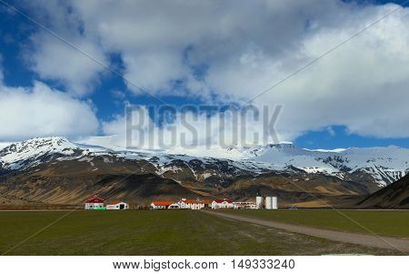Farm house near mountain under cloudy blue sky