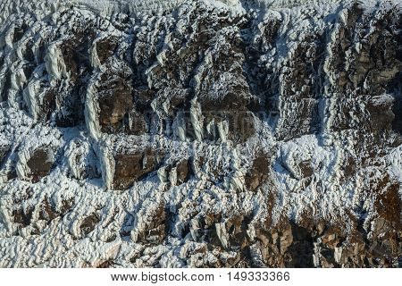 Frozen crystallized ice on sharp rocks as background texture