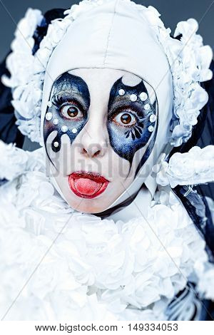 Close up portrait with cheerful female clown in a vintage style with a typical makeup