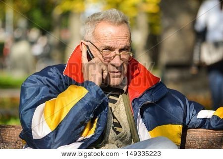 Good looking senior making phone call sitting on a bench in a park enjoying sun in bright autumn day
