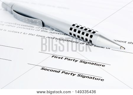 closeup of a pen on an unsigned contract