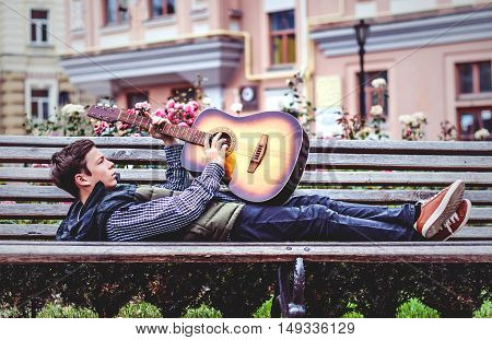 Young man while lying on the bench playing on acoustic guitar outdoor