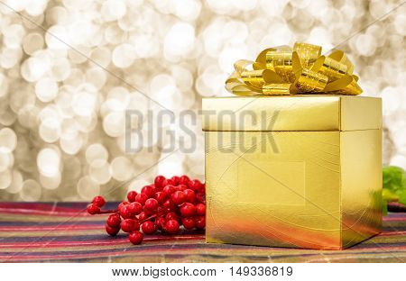 Gold Present Box With Ribbon On Table With Sparkling Gold Bokeh Light Background, Leave Space For Ad