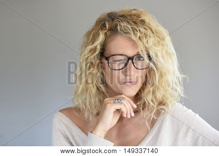 Portrait of blond woman with eyeglasses being expressive