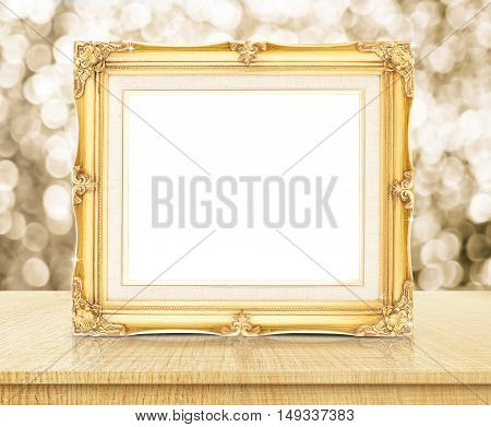 Blank Golden Vintage Photo Frame With Sparkling Gold Bokeh Wall And Wooden Table