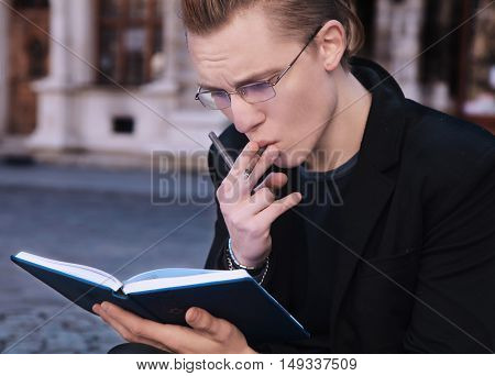 young student smoking and preparing for the exam in old center of europe city (education knowledge self-development self-improvement)