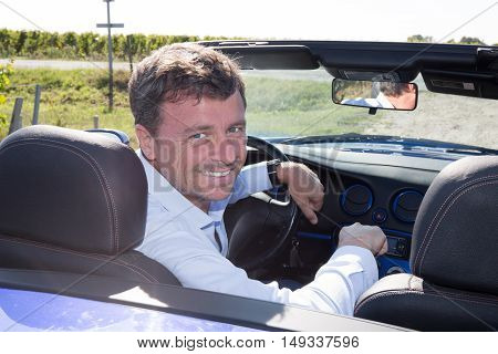 Man Happy In Blue Cabriolet Driving On Road Trip