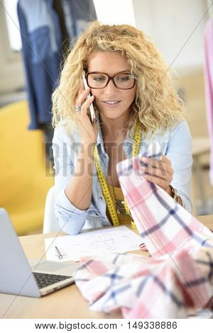 Woman fashion designer in office talking on phone