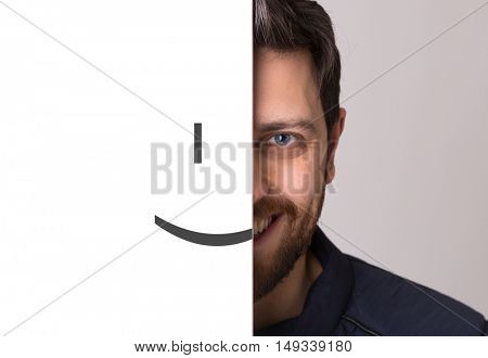 Young man covering half his face with a smiling emoticon