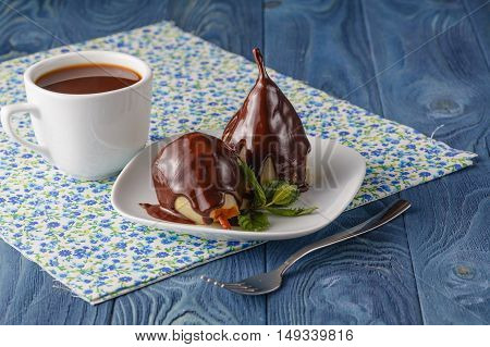 Dessert of pears with chocolate syrup on napkin