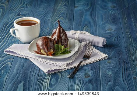 Pears In Caramel Syrup With Mint On A White Plate With Chocolate In The Background Against A Dark Ba