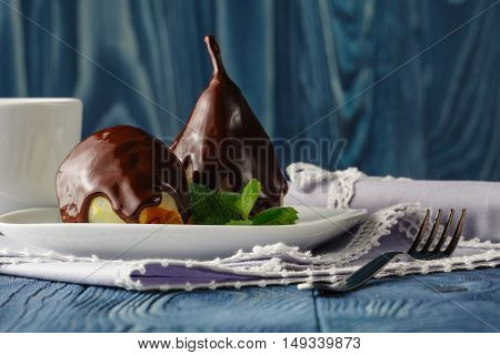 Pears with chocolate sauce on plate and naplin