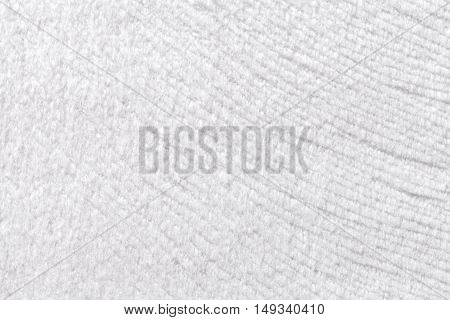 White background from a soft wool textile material closeup. Fabric with natural texture. Cloth backdrop.