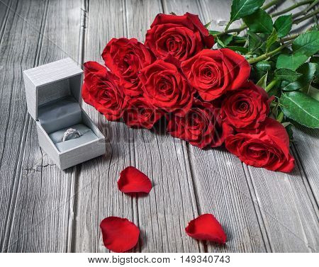 Red roses and a gift box on wooden vintage background/ Proposal/ Engagement rings/ Selective focus