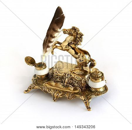 Ornate antique brass inkwell with feather and a figure of a horse