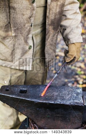 Blacksmith Holds Hot Steel Rod On Anvil