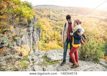 Beautiful young couple on a walk, standing on a rock against colorful autumn forest, woman holding binoculars