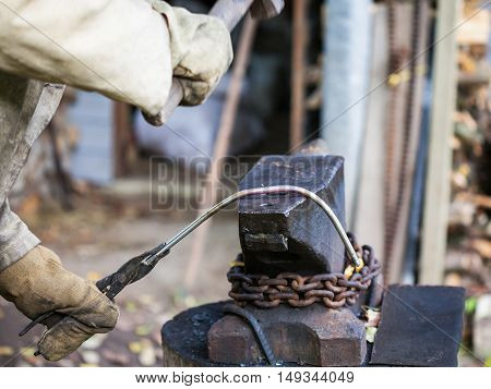 Blacksmith Forges Iron Rod On An Anvil