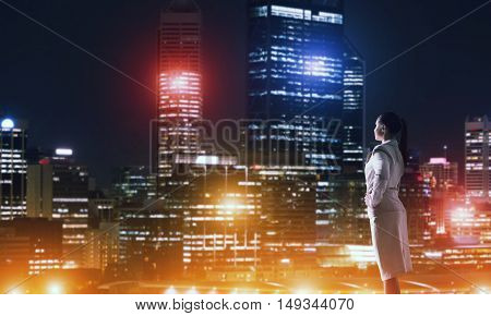 Side view of elegant businesswoman viewing lights of night city