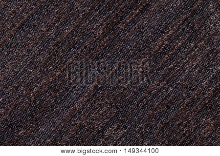 Dark brown background of a knitted textile material with diagonal pattern. Fabric with a striped texture closeup.