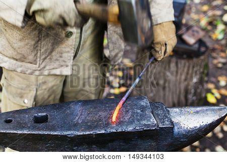 Blacksmith Hammering Red Hot Iron Rod On Anvil