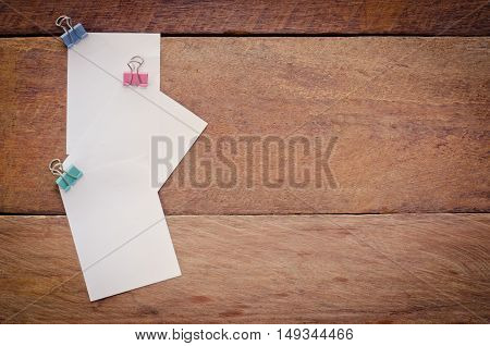 Note paper clip on a wooden floor.