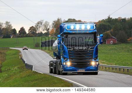 SALO, FINLAND - SEPTEMBER 24, 2016: Blue Scania R580 tank truck with bright high beams moves along rural road near dusktime. Scania's new truck range wins the 2017 International Truck of The Year Award.