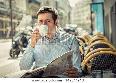 Businessman with newspaper sitting outdoor in restaurant under sunlight