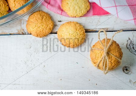Homemade coconut cookies on white wooden table with place for text. Freshly baked coconut cookies on rustic background. Cookies present. Selective Focus. Copy space.
