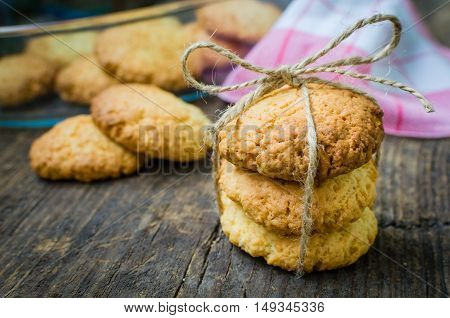 Homemade coconut cookies on dark old wooden table with place for text. Freshly baked coconut cookies on rustic background. Cookies present. Selective Focus. Copy space.