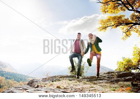 Beautiful young couple in sunny autumn nature, jumping on a rock