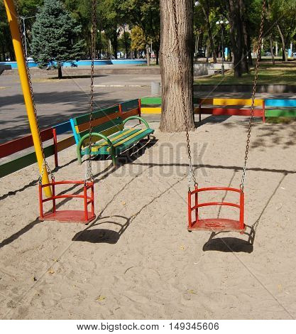 Red children's swing on a background of sand