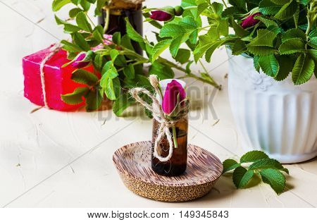 Rose essential oil in a glass bottle on a light table. Used in medicine cosmetics and aromatherapy. Fresh flowers green leaves and a piece of soap.
