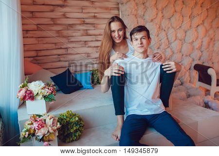 Young couple in love sitting embracing at home