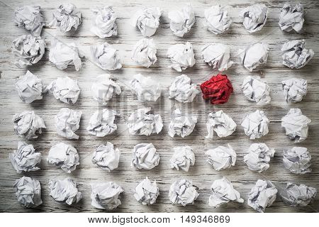 Set of crumpled white paper balls with one red ball.