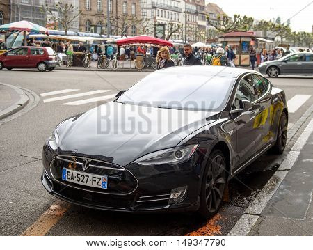 STRASBOURG FRANCE - MAy 14 2016: Young couple adimiring the beautiful Tesla Model S car parked in the center of the city - focus is on the car