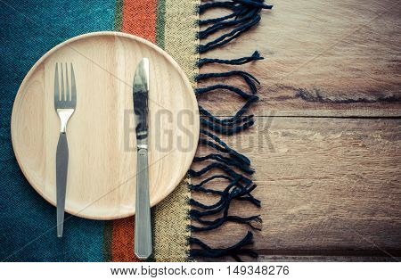 Knife and fork on a piece of wood and a scarf placed on a wooden table - still life.