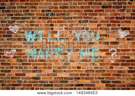 Brick wall with the text :  Wll you marry me?